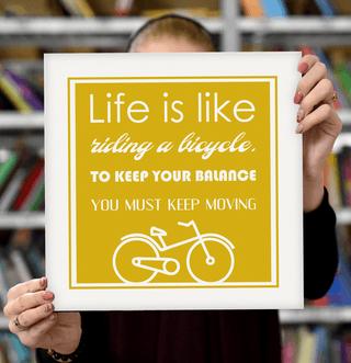 "Laimingų namų taisyklės ""Life is like riding a bicycle, to keep your balance you must keep moving"", geltona, 30 x 30 cm"