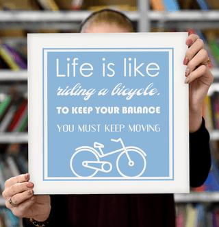 "Laimingų namų taisyklės ""Life is like riding a bicycle, to keep your balance you must keep moving"", žydra, 30 x 30 cm"