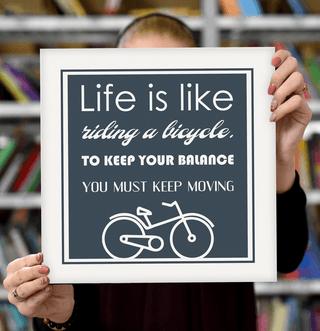 "Laimingų namų taisyklės ""Life is like riding a bicycle, to keep your balance you must keep moving"", pilka, 30 x 30 cm"